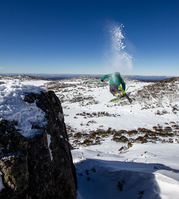 Skier jumps of big boulder Mount Wheatley, Perisher
