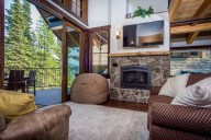 The cozy living room has spectacular views, a high-def TV, and a gorgeous gas fireplace [Tamarack]