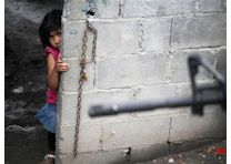 A girl peeks from behind a wall as a police officer patrols a neighborhood in Guadalupe April 13, 2012. REUTERS/Daniel Becerrill.