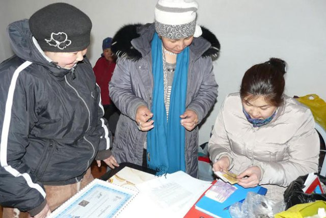 SLE's Cholpon Abasova (right) counting a community's bonus payment