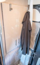 The clothes closet in the bathroom - we added some over the door hooks for our everyday jackets and such. The shower curtain attaches around the ceiling to make a shower stall in the center and keep the walls dry.