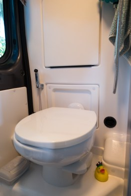 Porcelain toilet under the sink that flips down. The shower curtain attaches around the ceiling to make a shower stall in the center and keep the walls and toiletdry.