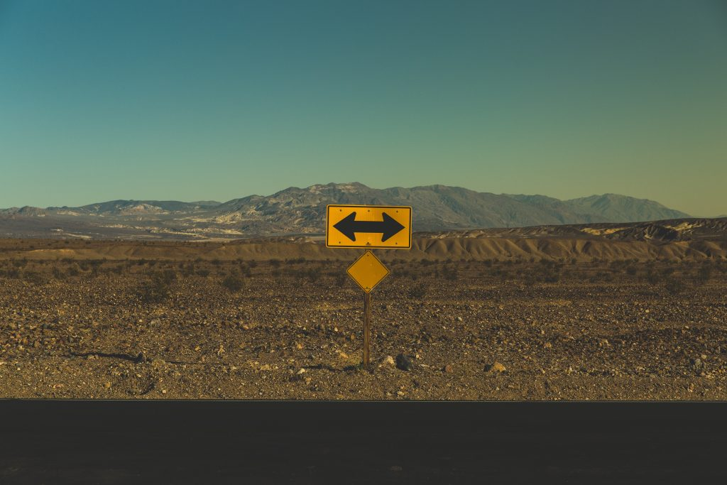 Directional road sign pointing left and right on roadside in the desert