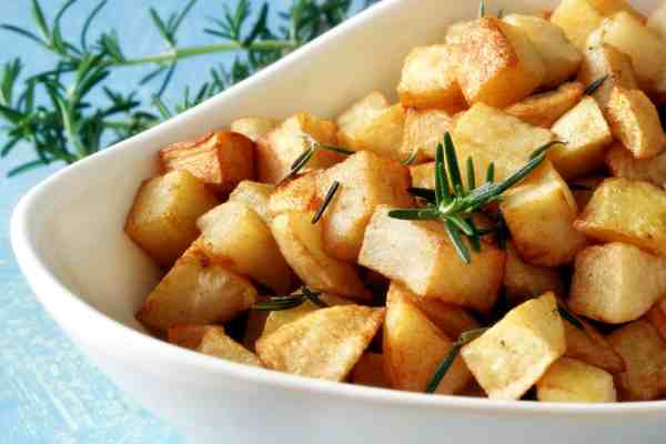 crispy roasted potatoes in a white bowl with rosemary