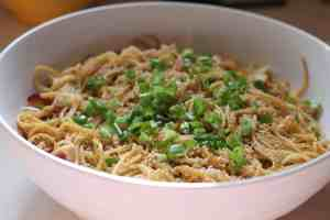 white bowl containing chicken lo mein with green onions and sesame seeds on top
