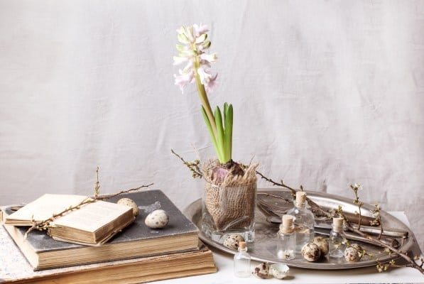 vintage decorate books next to a tray with flowers and knick knacks