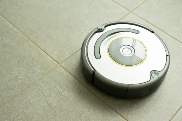 Roomba running across a kitchen floor