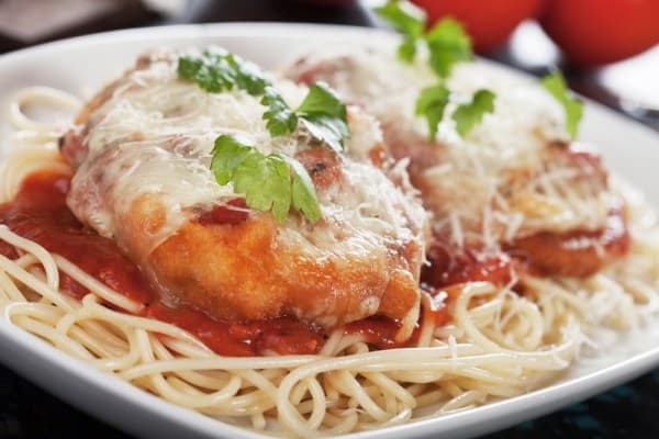 easy chicken parmesan recipe on a white plate with pasta
