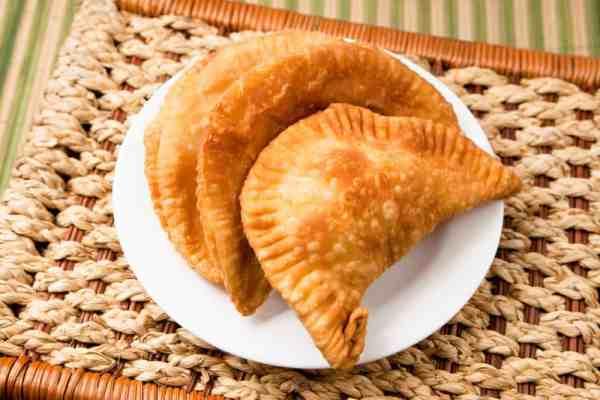 Cheese empanada, meat empanada or chicken empanada, on a white plate. Empanada (meat pie) - traditional snack originally from Spain.