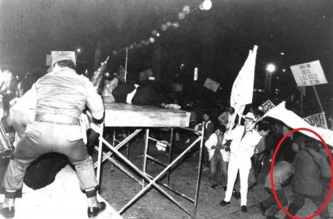 En la fotografía de José Herchel Ruiz se observa cuando el individuo de la ametralladora se desplaza hacia la multitud que por el ruido de los disparos huye despavorida. En el camino pasa muy cerca de los cómplices del asesinato de Galán que aún mantienen en sus manos la pancarta que sirvió para efectuar el atentado. No se entiende porque el uniformado que aparece de espaldas a la cámara y que paradójicamente también carga una ametralladora no actuó.