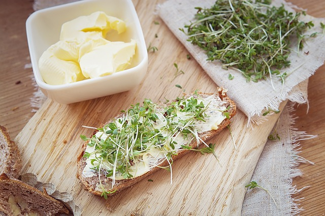 butter in a dish next to slice of homade bread. Cress on top of butter.