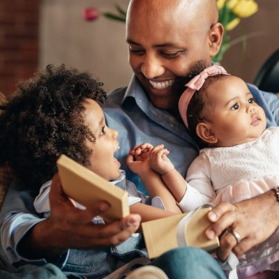 young-boy-smiles-at-father-holding-baby-sister_square