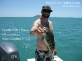 Angler holding spotted bay bass with Las Islas Encantadas in the background.