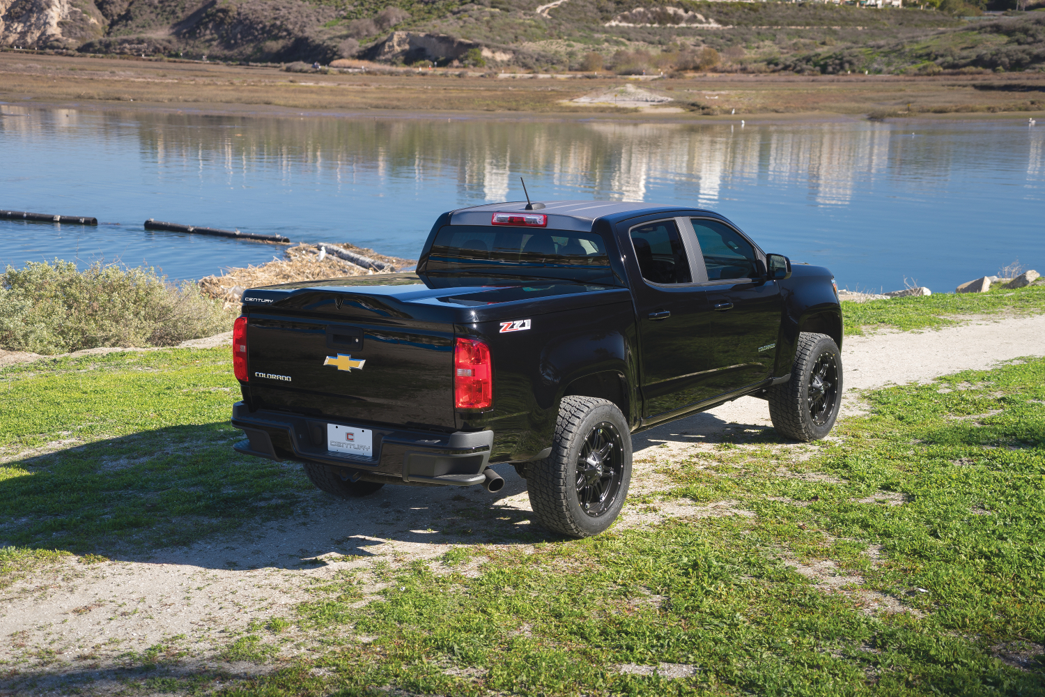 The Century Tonneau Cover Silhouette shown installed on a Chevrolet Colorado taken in front of a lake front.