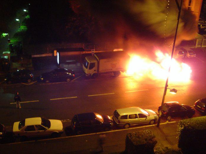 Bil i brand i Grande rue de Sèvres (92) den 3. november 2005 under optøjerne fra 2005. Own work Author A.J. (CC BY-SA 3.0)