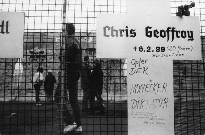 Commemorative tablet to Chris Gueffroy. In the background is the partly destroyed Wall, near Reichstag. Winter 1989/90. Source: Wikipedia: https://simple.wikipedia.org/wiki/Chris_Gueffroy