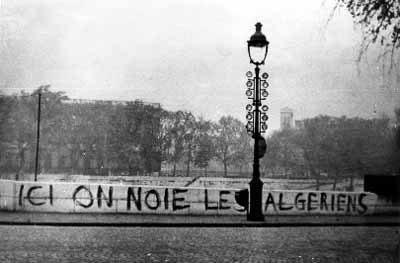 """""""Her druknede vi algierne"""". Banner på bro over floden Seine i Paris."""