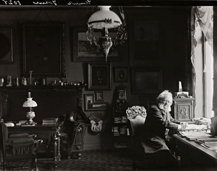 Henrik Ibsen i sitt arbeidsværelse i Arbinsgate 1, Oslo, Norge, 1897/1898. Photo: L. Szacinski [atelier] Ejes af: Nasjonalbiblioteket / National Library of Norway. Kilde: www.nb.no. Billed nr. bldsa_ibf2a1001b. Public domain. Se nedenfor 20. marts 1828.