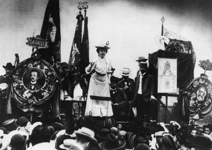 Rosa Luxemburg addresses a Stuttgart crowd in 1907. Here she is flanked by portraits of Karl Marx (right) and Ferdinand Lassalle (left), the founders of the German Socialist movement.