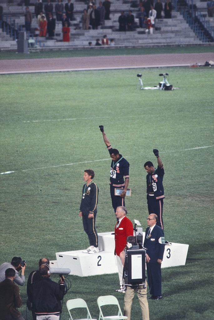American sprinters Tommie Smith and John Carlos, along with Australian Peter Norman, during the award ceremony of the 200 m race at the Mexican Olympic games. During the awards ceremony, Smith (center) and Carlos protested against racial discrimination: they went barefoot on the podium and listened to their anthem bowing their heads and raising a fist with a black glove. Mexico City, Mexico, 16 October 1968. Source: http://www.gettyimages.co.uk/detail/news-photo/the-american-sprinters-tommie-smith-john-carlos-and-peter-news-photo/186173327 Photo: Angelo Cozzi (Mondadori Publishers) Public Domain.American sprinters Tommie Smith and John Carlos, along with Australian Peter Norman, during the award ceremony of the 200 m race at the Mexican Olympic games. During the awards ceremony, Smith (center) and Carlos protested against racial discrimination: they went barefoot on the podium and listened to their anthem bowing their heads and raising a fist with a black glove. Mexico City, Mexico, 16 October 1968. Source: http://www.gettyimages.co.uk/detail/news-photo/the-american-sprinters-tommie-smith-john-carlos-and-peter-news-photo/186173327 Photo: Angelo Cozzi (Mondadori Publishers) Public Domain.