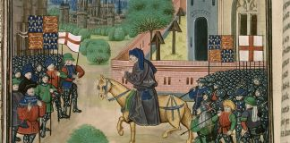 """An illustration of the priest John Ball (""""Jehã Balle"""") on a horse encouraging Wat Tyler's rebels (""""Waultre le tieulier"""") of 1381, from a ca. 1470 manuscript of Jean Froissart's Chronicles in the British Library. There are two flags of England (St. George's cross flags) and two banners of the Plantagenet royal coat of arms of England (quarterly France ancient and England), and an implausible number of unmounted soldiers wearing full plate armour among the rebels. Source: Detail of British Library manuscript """"Royal 18 E. I f.165v"""" as scanned at http://molcat1.bl.uk/IllImages/Ekta/big/E025/E025825.jpg (see also here). Author: Unknown medieval artist illustrating Froissart's Chronicles. Public Domain"""
