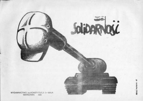Plakat med sikkerhedshjelm hængt over tankens kanon. 1980