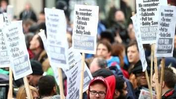 Holding placards with some of her sins !