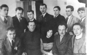Fotos af sovjetiske digtere og forfattere ved Sovjetforfatterens første allianceskongres (1934) Kovalenkov AA stående, tredje fra højre ved siden af Sergei Mikhalkov. Foruden dem sidder i første række fra venstre mod højre: Alexander Shevtsov, Vladimir Stavsky, Margarita Aliger, Alexander Bezymensky, Alexander Isbakh. I anden række: Sergey Vasilyev, Grigory Brovman, Evgeny Dolmatovsky, ..., Ilya Frenkel, Vasily Sidorov. Dato 1934. Photo: Ukendt Kilde: http://www.viskra.ru/2013/03/blog-post.html. Public Domain.