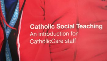 """Cover of """"Catholic Social Teaching: An introduction for CatholicCare Staff"""" by Sandie Cornish. Photo of two smiling adults with disabilities."""