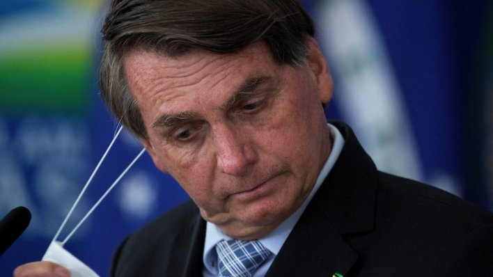 Brazilian President Jair Bolsonaro removes his mask during the signing ceremony of bills to expand the capacity to purchase vaccines by the Federal Government, at the Planalto Palace, in Brasilia, Brazil, 10 March 2020.