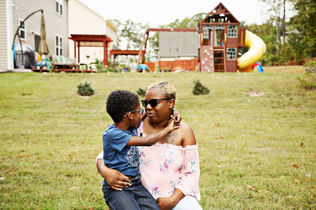 Laura Miles holds her oldest living son, Dasan, 7, in the family's Durham backyard on Oct. 5, 2019