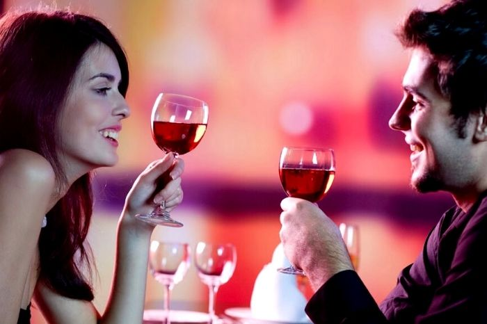 man and woman smiling while drinking a glass of red wine on a date