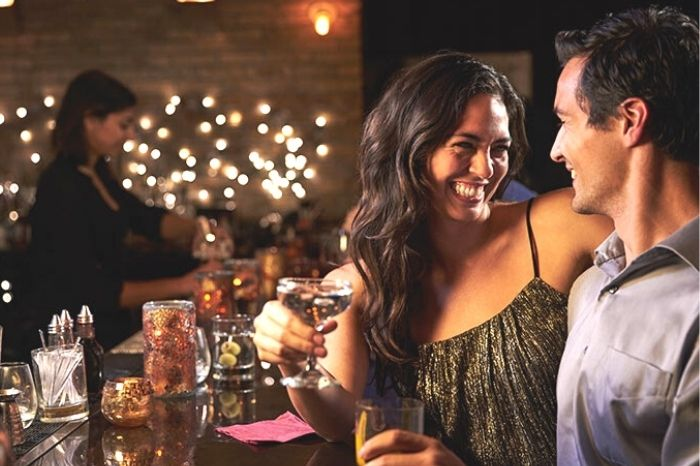 man and woman smiling with beer and cocktail on a date in a bar with fairy lights in back ground