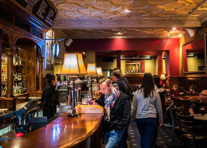 man seated at young and jacksons hotel traditional bar with refurbished heritage listed interior