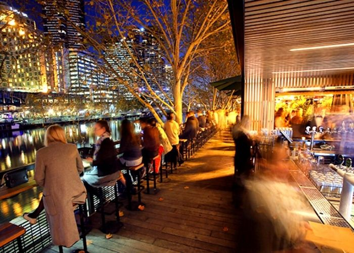 people seated on stools along arbory bar and eatery our door bar over looking south bank on yarra river just off flinders walk in cbd