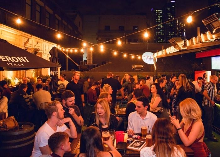 large tables of seated patrons with beers at Campari House rooftop bar at night under hanging lights in CBD