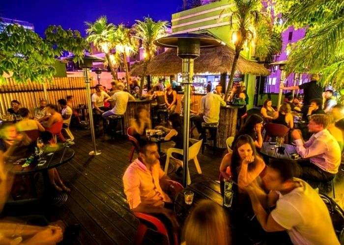 group of people seated under heaters at night at palmz rooftop bar of the Carlton club with palm trees on Bourke street