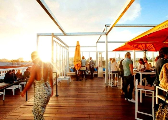 Stunning views from the Emerson Rooftop lounge with people drinking with yellow umbrellas and blue sky