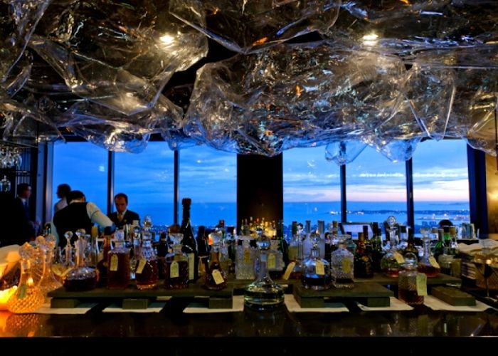 ocean views from the lui wine and champagne bar on rialto with bar tenders mixing drinks and alcohol bottles in foreground