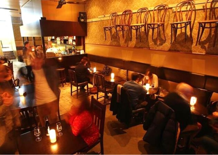 diners eating inside cabinet bar and balcony hidden bar restaurant with candles on tables on 11 rainbow alley cbd