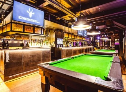 sports tv screen and green pool table at diesel