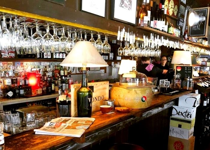 hanging wine glasses with lamp and news paper on counter of small corner restaurant of diksteins corner bar on little collins street in city
