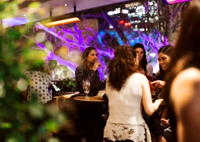 four women seated at duke of wellingtop pubs rooftop bar drinking wine at night on flinders street cbd