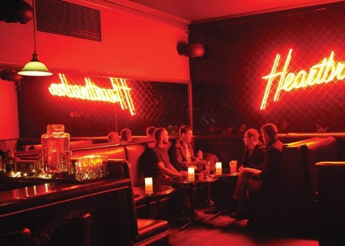 four men seated in booth below heartbreaker sign in russell street