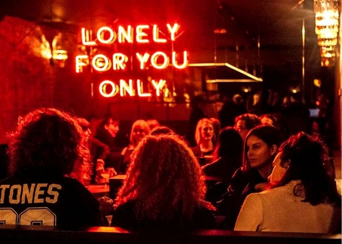 groups of patrons sitting at gogo cocktail bar at night with red glowing lonely for you only sign on Flinders lane