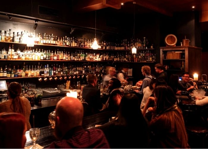 two bar tenders making cocktails and groups of seated people ordering drinks from eau de vie whisky room