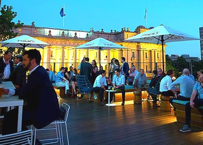 evening crowds seated on the rooftop bar under white umbrellas of imperial hotel overlooking Melbourne parliament house on Bourke street