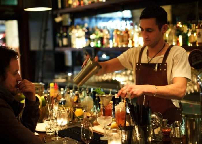male bar tender with red apron pouring cocktail for lady at joe taylor bar on errol street