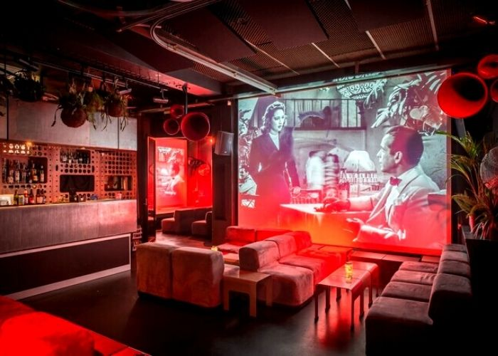 large projector screen showing vintage film in Loop Project Space and Bar with red velveted couches, hanging plants and decretive lighting in creative meeting space