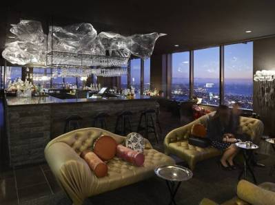 decrotive cream leather couches with lady seated at rooftop lui bar with city views
